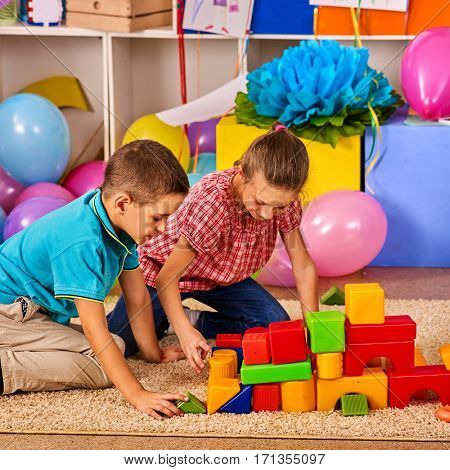 Children playing in kids club indoor. Lesson in primary school. Boy and girl together play. Kindergarten child sit on floor with balloon