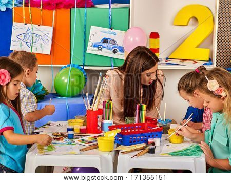 Children painting and drawing in kids club. Craft lesson in primary school. Kindergarten teacher who smiling help small students. Kid boy and girl coloring picture on table in class. Balloons on