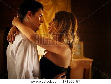Couple dancing and kissing indoor. Romantic evening interior for loving couple. Happy people in love. A lot of pictures in room.