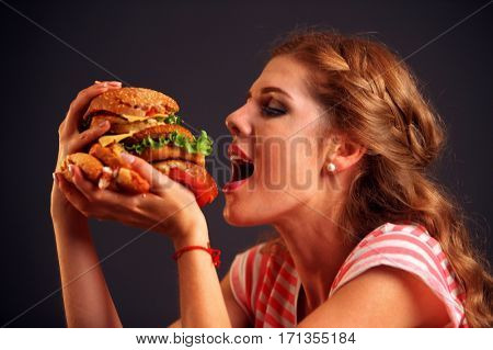 Woman eating sandwich. Girl with pleasure eats burger after diet. She opened her mouth, holding a hamburger on his outstretched hands and closed her eyes. Student with meal on black background.