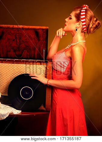 Retro woman with music vinyl record and gramophone. Pin-up retro female style. Girl pin up style wearing red dress standing in profile and full height