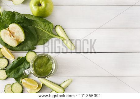 Detox cleanse drink background. Green smoothie ingredients. Natural healthy juice in glass jar for diet or fasting day. Cucumber, apple, lime and spinach mix on white wood top view with copy space