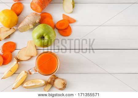 Detox cleanse drink background, vegetable smoothie ingredients. Natural healthy juice in glass jar for diet or fasting day. Carrot, apple, ginger and lemon mix on white wood, top view with copy space