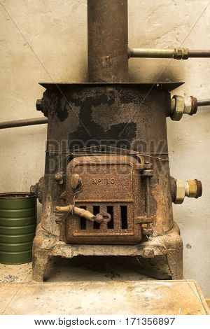 Antique metal rocket stove in working condition against a brown wall