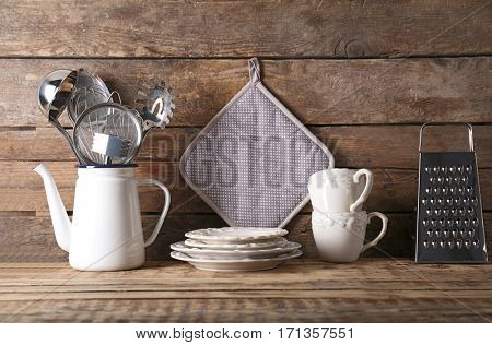 Cooking utensils and dishware on wooden background