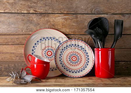 Kitchen utensils and dishware on wooden background