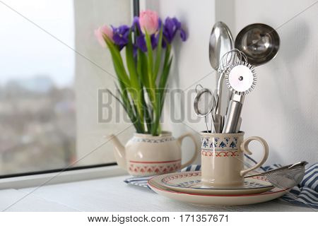 Kitchen utensils in cup and flowers on windowsill