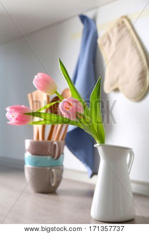 Tulips in vase and kitchen utensils on background
