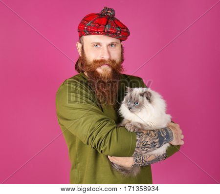 Young bearded man in plaid cap with fluffy cat on color background