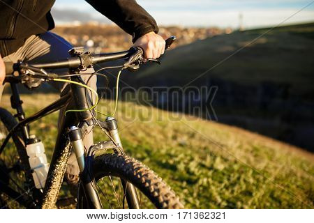 Closeup of cyclist hand on handlebar. Unrecognizable sportsman riding his bicycle on sunny spring day. Travel in the countryside. Detaik of the bicycle. Helm. Green field and grass.