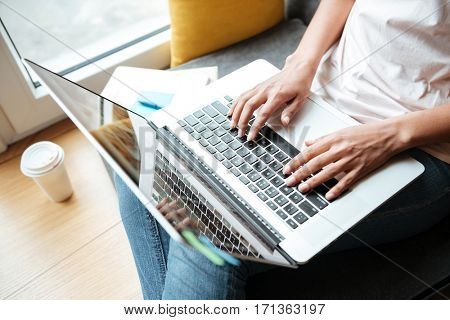 Top view of African Woman sitting near the window with laptop in library