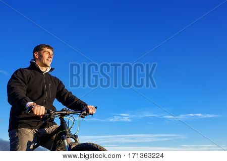 Mountain Biker and blue sky background. Detail of the bicycle. Helm. Blue sky with clouds. Cyclist's face and hands. Travel in the countryside. Sport and lifestyle.