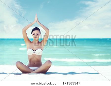 Beautiful and sexy young girl meditating on a summer beach. Recreation and healthy lifestyle concept.
