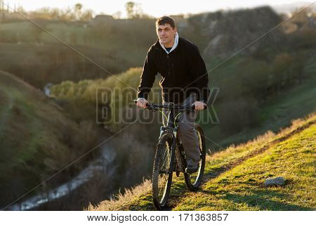 Cyclist Riding the Bike on the Beautiful Spring Mountain Trail. Travel in the countryside. Beautiful landscape with hill, trail and green grass. Healthy lifestyle. Sunrise.