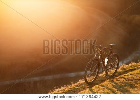 Mountain bicycle standing in the hill trail. Nobody's here. Travel in the countryside. Sunny day. Spring season. Sunrise. Beautiful Landscape with hill and trail.