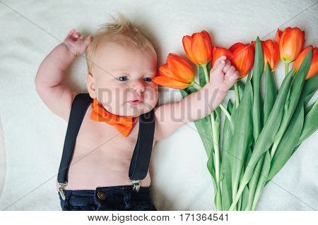 beautiful little baby lying near a bouquet of red tulips