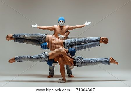 The group of gymnastic acrobatic caucasian men posing in balance posture on gray studio background in hats and masks