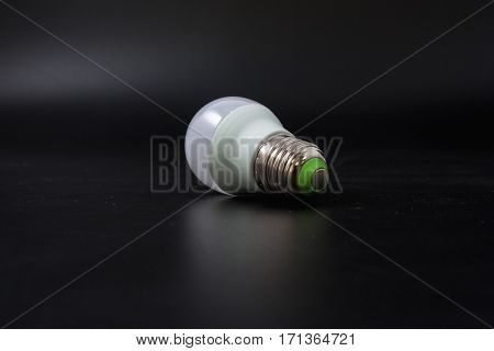 Economical Light Bulb On A Black Background.