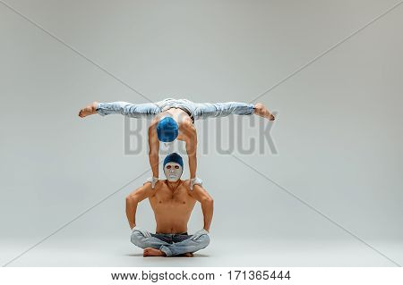 The two gymnastic acrobatic caucasian men posing in balance posture on gray studio background in hats and masks