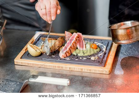 Decorating delicious restaurant dish with tune steak on the kitchen