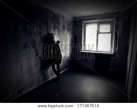 Girl in an abandoned creepy room. Ghost in Haunted house