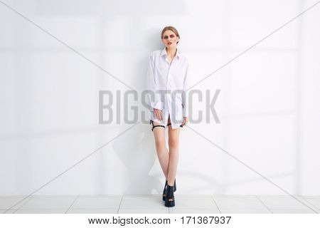 Young extravagant model near light wall