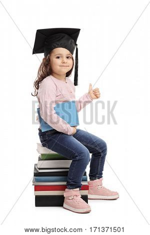 Little girl with a graduation hat sitting on a pile of books and giving a thumb up isolated on white background