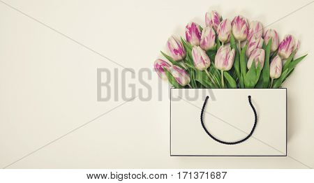 Tulips in shopping bag with space for text. Flat lay, top view