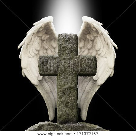 Ancient Stone Cross and Guardian Angel Wings - old masonry cross with a pair of white angel wings behind on a black background with a shaft of central white light