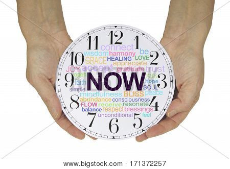 There is always only NOW - female hands holding a clock face with a NOW word cloud isolated on a white background
