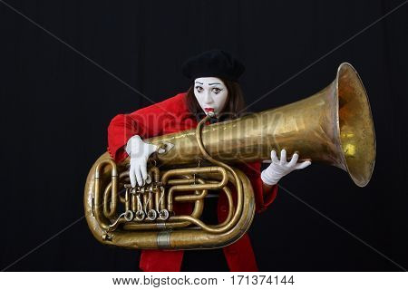 brunette girl in mime costume holding tube (a wind instrument)