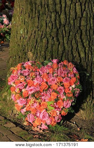 Heart shaped sympathy or funeral flowers near a tree
