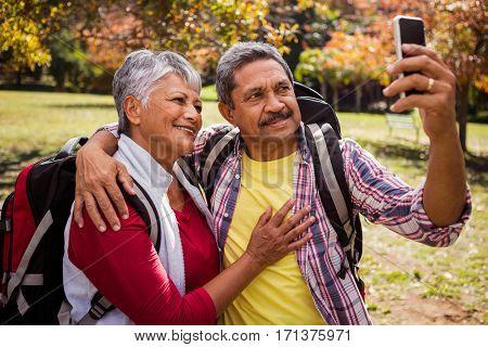 An elderly couple walking taking a selfie in the aprk