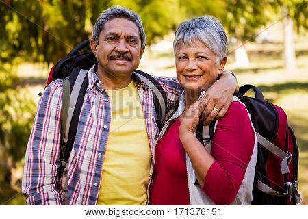 Portrait of hiker couple embracing in a park