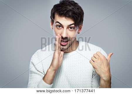 young handsome man dissolves gossip standing next to color background in photostudio