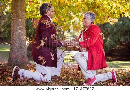 Side view of cheerful mature couple kneeling on autumn leaves in park