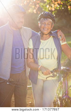 Portrait of mature couple holding cycling helmet in a park