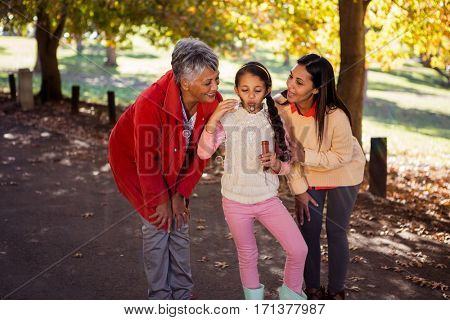 Girl blowing bubble with family at park