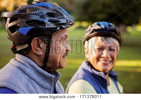 Close up of mature couple holding cycling helmet in a park
