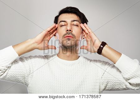 portrait of young handsome man with closed eyes posing in photostudio next to the color background