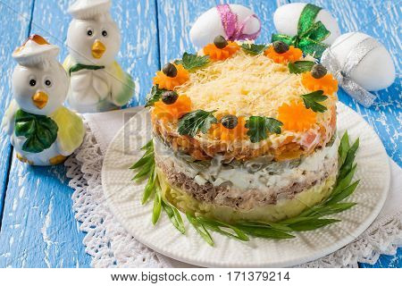 Multilayer festive salad with tuna vegetables and eggs on a blue wooden table with eggs and chicks. Easter food Easter recipe. Selective focus