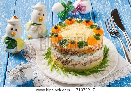 Multilayer festive salad with tuna vegetables and eggs on a blue wooden table with eggs and chicken. Easter food Easter recipe. Selective focus