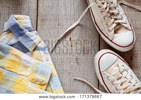 Shirt and sneakers on the old wooden floor.