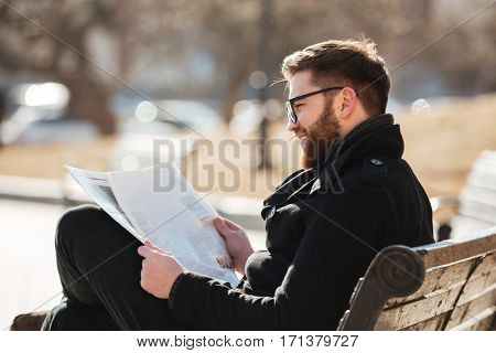 Smiling bearded young man in glasses reading newspaper on the bench outdoors