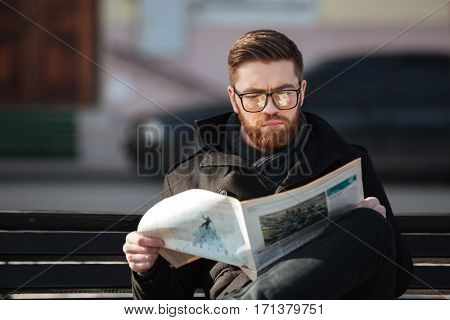 Concentrated bearded young man in glasses sitting on bench and reading newspaper outdoors