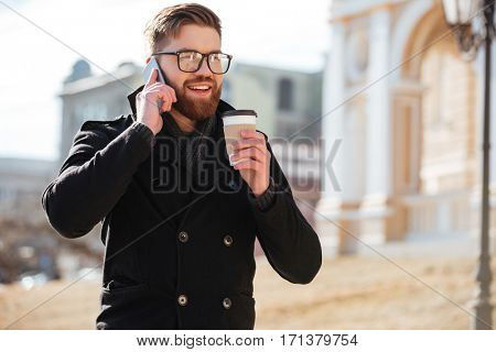 Happy bearded young man talking on cell phone and drinking coffee in the city