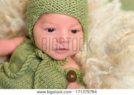 Adorable baby in a knitted green outfit, with his eyes wide opened, resting, closeup