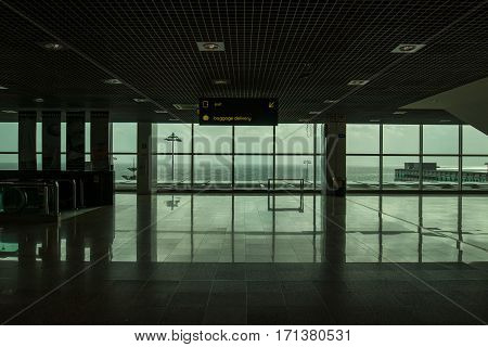 Madeira's airport exit completly empty with a great panoramic view to the ocean in green tone due to the windows glass.