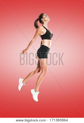 Full length portrait of an attractive excited fitness girl in sportwear jumping isolated over red gradient background