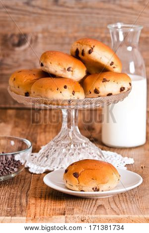 Chocolate chip brioche on glass tray with milk bottle.